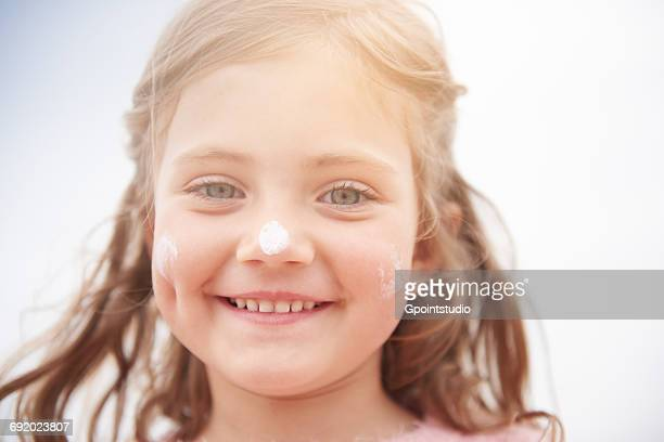 Little girl with sun cream on nose