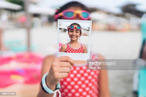 bambina con google nuoto che mostra foto istantanee - vacanza al mare foto e immagini stock
