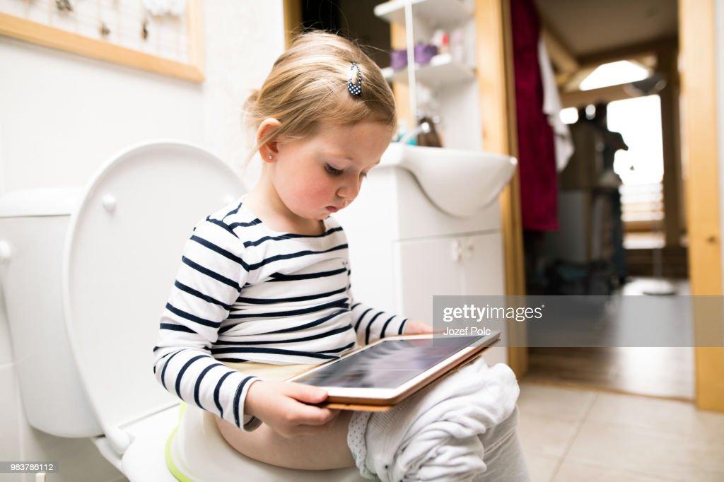 Happy Little Girl Sitting On The Toilet Potty Training