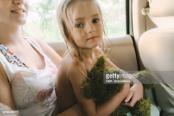 little girl with teddy bear in car - mama bear stock photos and pictures