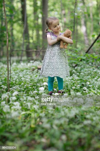 Little girl with teddy bear, standing amongst wild garlic in woodland