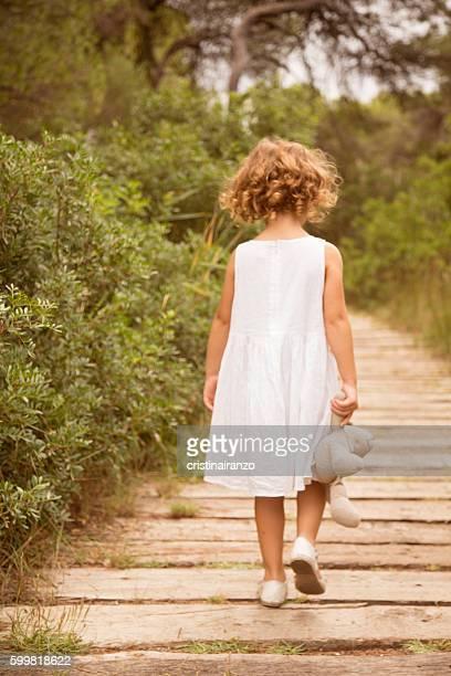 Little girl with teddy walking