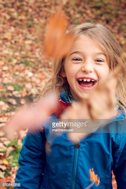 Little girl with tooth gap playing with autumn fallen leaves.