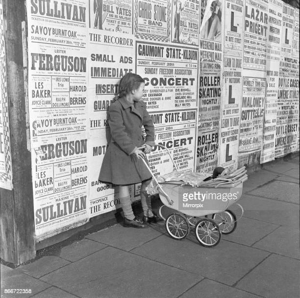 Little girl with toy pram stands waiting for her mother against a background of adverts for shows and entertainment on the Harrow Road 26th March 1954