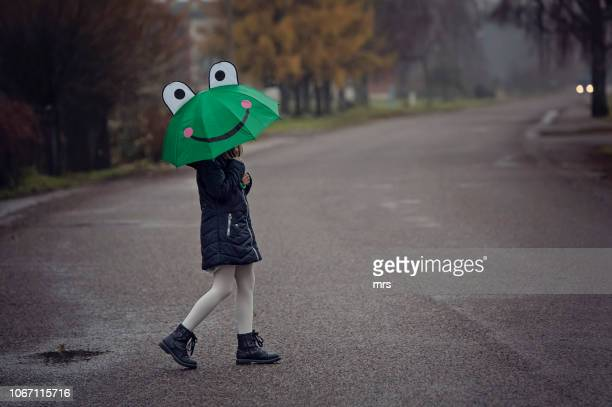 little girl with umbrella - frog stock pictures, royalty-free photos & images