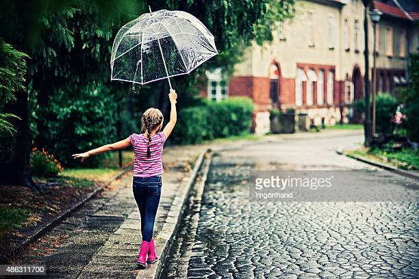 Little girl with umbrella walking in rain.