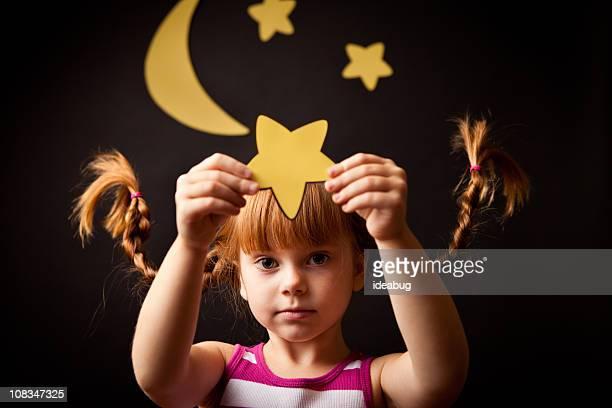 Kleines Mädchen mit nach oben, geflochtener Zopf stehen unter Mond Holding Sternen
