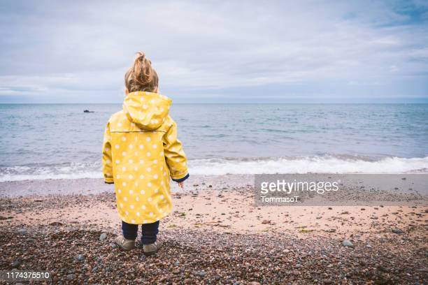 little girl with yellow raincoat on the beach in autumn rainy day - solitude stock pictures, royalty-free photos & images