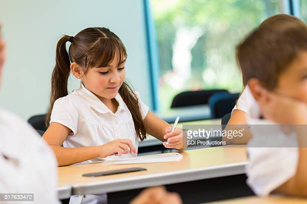 Little girl works on assignment in private school