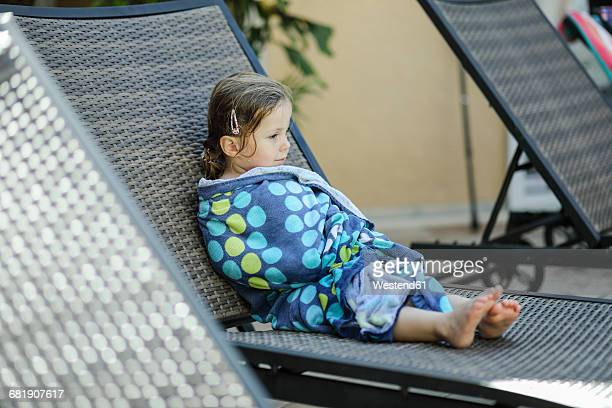 Little girl wrapped in bath towel relaxing on sunbed