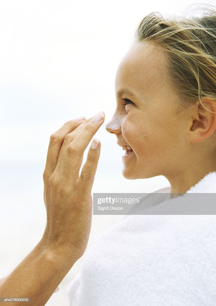 Little girl wrapped in towel having sunscreen rubbed into nose by mother : Stockfoto
