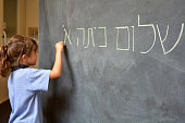 Little girl writes Hello First Grade greetings in Hebrew