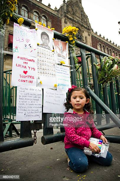 A little girl writes message outside the National Palace for the 43 missing students from Ayotzinapa