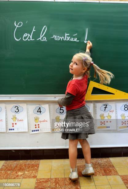 A little girl writes on the blackboard 'C'est la rentrée' at the school Jules Ferry in Bethune northern France on August 28 a few days of the start...