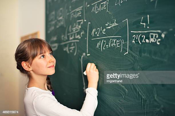 Little girl writing difficult mathematics equations