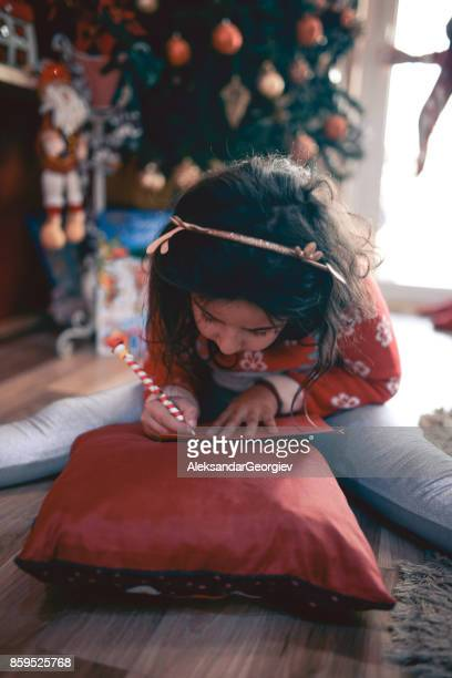 little girl writing her wishes on letter to santa under christmas tree - messaggio foto e immagini stock