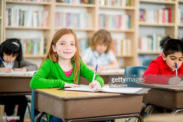 little girl writing in class - black ginger baby stock photos and pictures