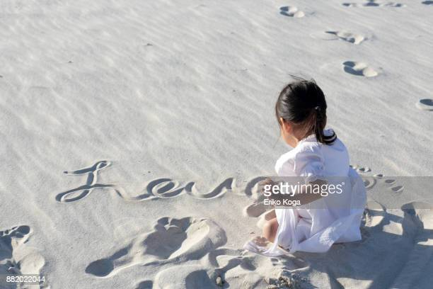 Little girl writing letters on beach
