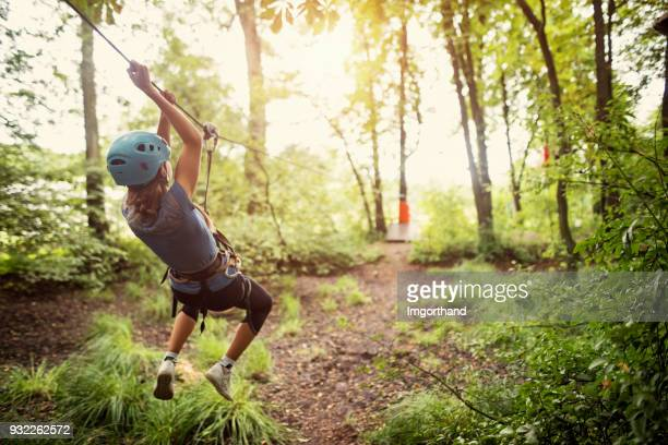 Little girl ziplining in forest