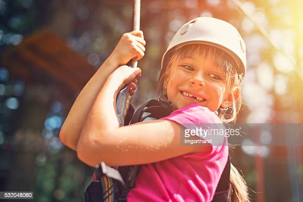 Little girl zipping in zip line adventure park