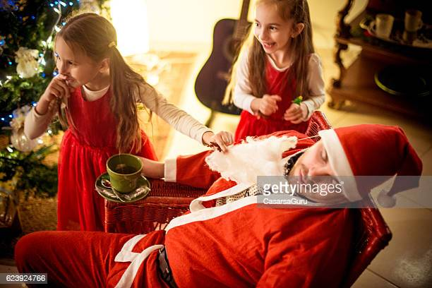 little girls and a family member dressed as santa - naughty santa stock photos and pictures