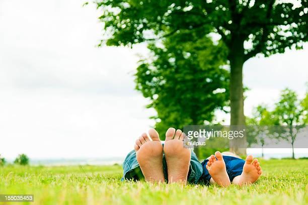 Kleines Mädchen mit Vater die Füße mit Gänseblümchen-Blumen