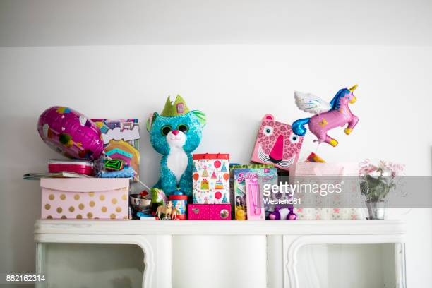 little girl's birthday presents on a cabinet - funny birthday stock photos and pictures