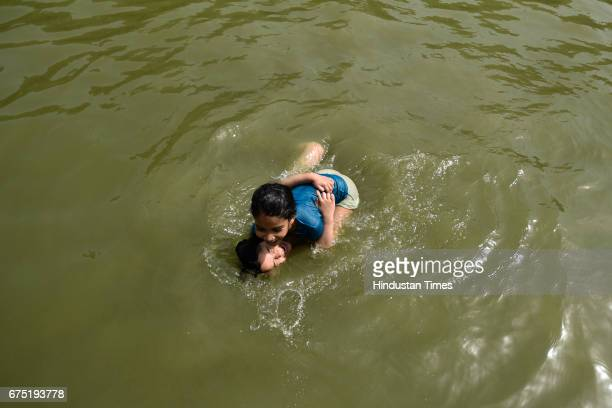 Little girls cool off in a water channel on a hot summer day near India Gate on April 30 2017 in New Delhi India