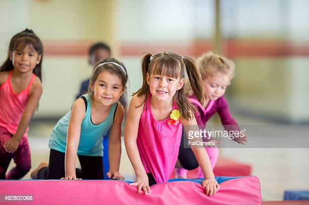 Little Girls Crawling Over Mats at the Gym