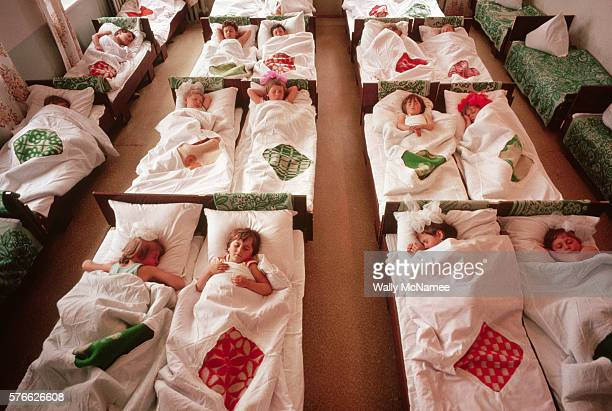 Little girls curl up for their naps at the Lenin Collective Farm's day care center, where they are looked after while their parents are working. |...