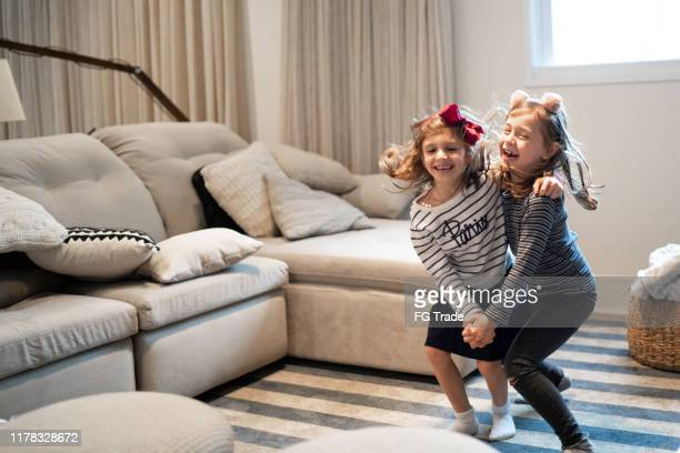 little girls dancing in living room - children only stock pictures, royalty-free photos & images