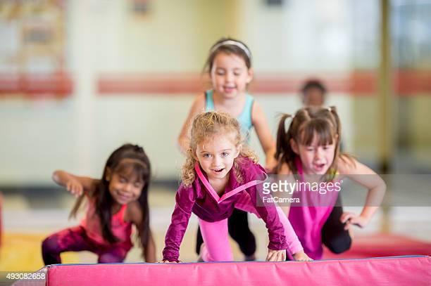Kleine Mädchen machen ein Fitnessstudio Hindernisparcours