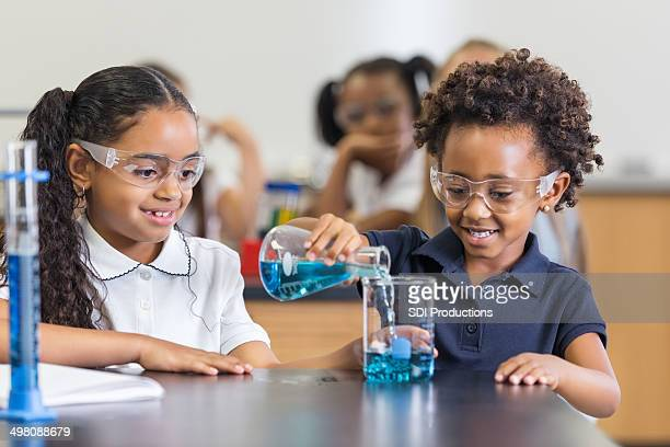 Little girls doing science experiement together in private school classroom