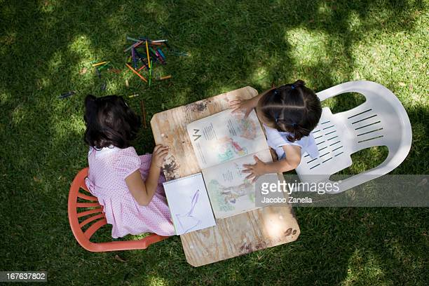 Little girls drawing coloring books in the garden