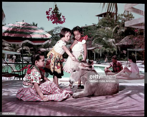 Little girls dress in native clothes sit with a donkey in Acapulco Mexico in July 1953