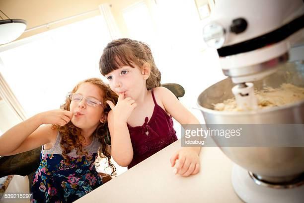 女の子クッキーの生地を食べるのキッチンカウンターからミキサ