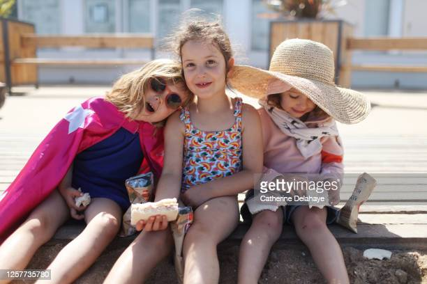3 little girls eating sandwiches on the beach - innocence stock pictures, royalty-free photos & images