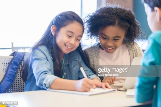 little girls enjoy writing together at school - state school stock pictures, royalty-free photos & images