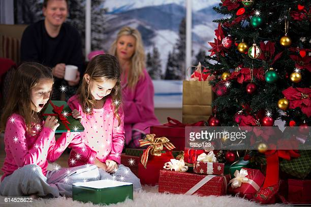 Little girls excitedly open Christmas presents.