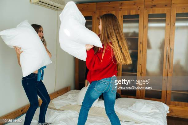 Little Girls Fighting With Pillows On The Bed