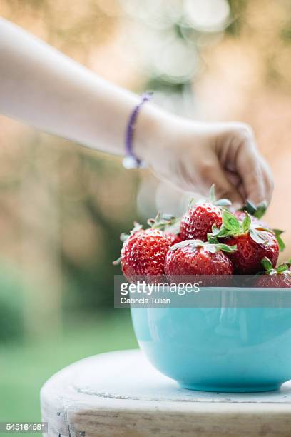 Little girl's hand grabbing a fresh strawberry