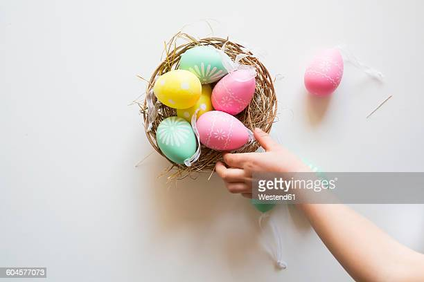 Little girl's hand taking coloured Easter egg