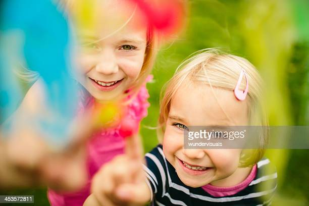 Little girls having fun with colors and finger paint