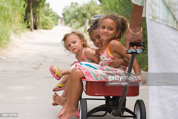 little girls in a wagon - toy wagon stock photos and pictures