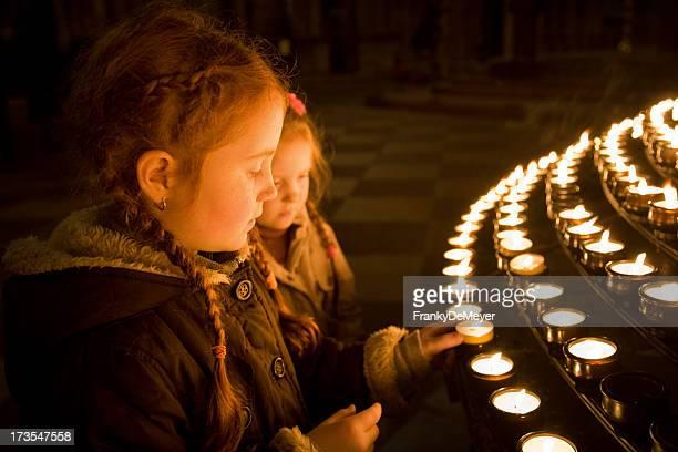Niñas en church, iluminación velas
