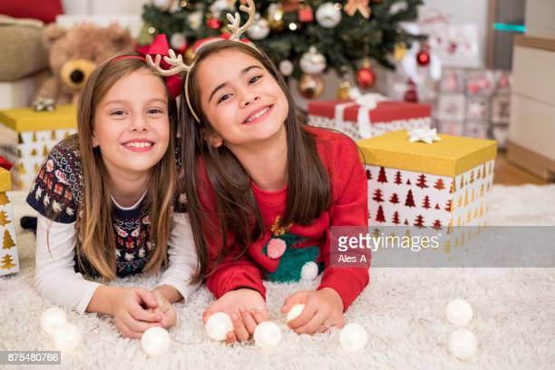 little girls in front of a christmas tree - next to stock pictures, royalty-free photos & images