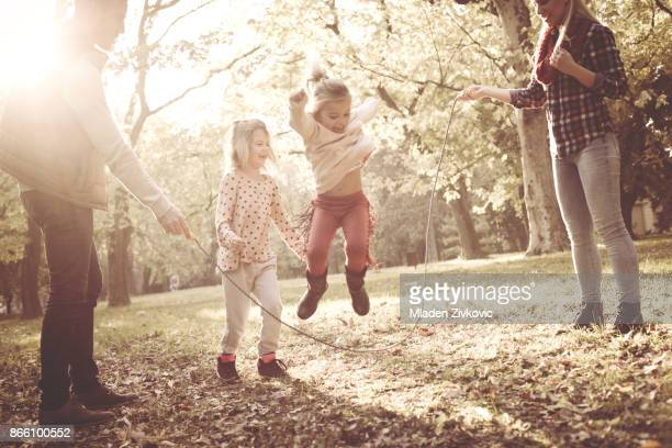 Little girls  jumping across jump rope and parents holding rope in park.