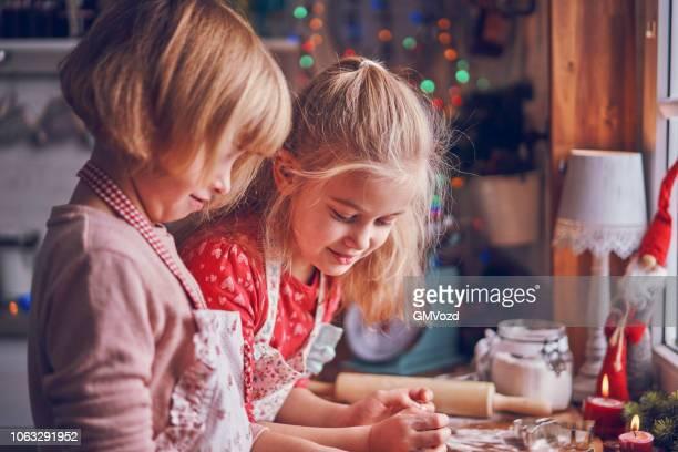 kleine mädchen kneten von teig für weihnachtsplätzchen - backen stock-fotos und bilder