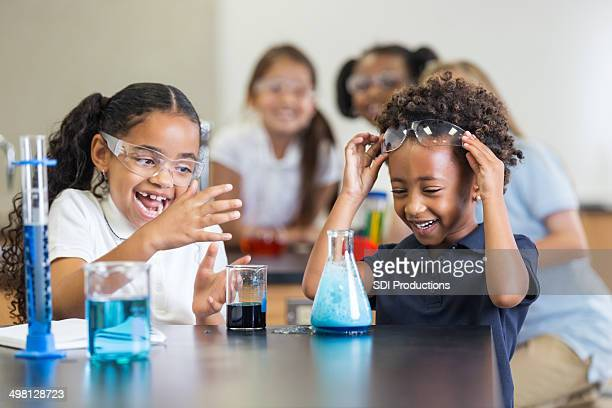 Little girls laughing while doing science experiment in classroom
