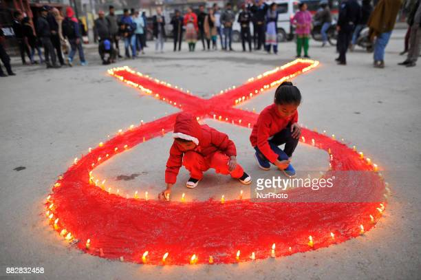 A little girls lit candles around the symbol of RED AIDS during Eve of World AIDS Day celebrated in Kathmandu Nepal on 1st Dec 2017 World AIDS Day is...